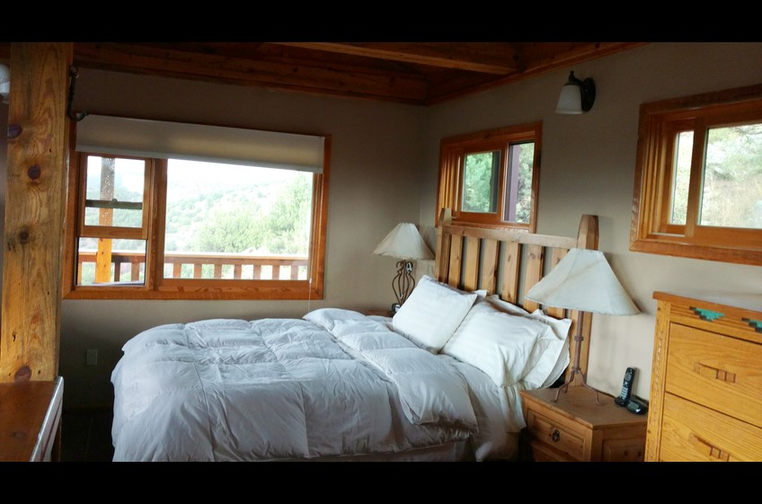 The bedroom with down comforters, hotel quality mattress at Bear Creek Canyon Retreat, New Mexico Cabin Rentals.