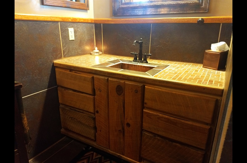 A custom bath vanity built with repurposed aged oak from what was once the K-12 school in Mule Creek NM (about 33 miles from Gila).  The school was built sometime in the 1930's.