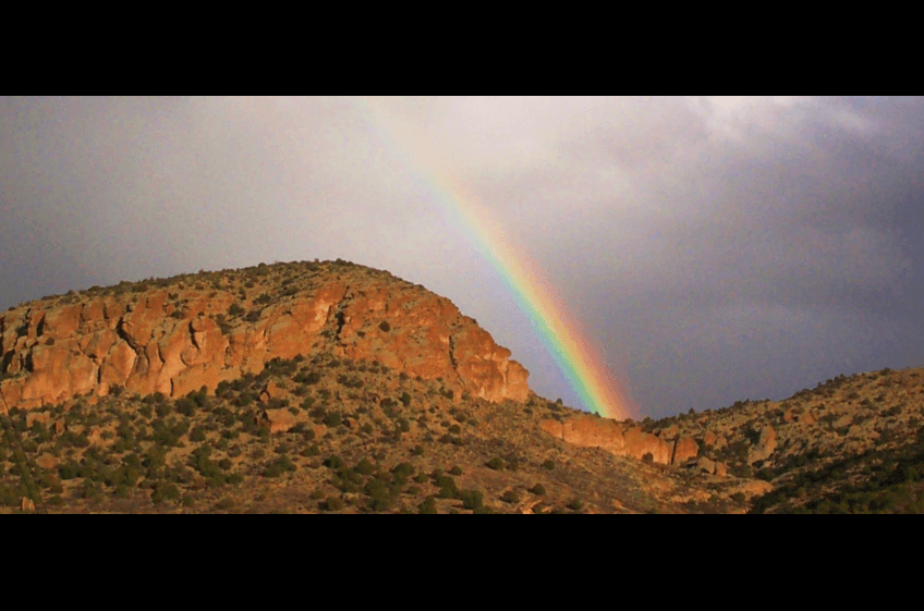 An afternoon thunderstorm creates a rainbow over Turtle Rock at New Mexico Cabin Rentals